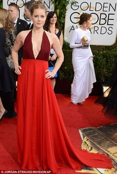 1-12-14.   Lady in red: American Hustle nominee Amy Adams sported a Valentino two toned plunging gown and chic braided updo at the Golden Globes Awards on Sunday at the Beverly Hilton