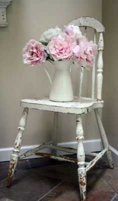 Lovely vintage shabby chic chair for bedroom decor with a vase of flowers to dress up a corner of the room.