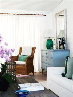Vita gardiner i vardagsrummet döljer en skuggig veranda. Byrå i gustaviansk stil, korgstol från Bru...