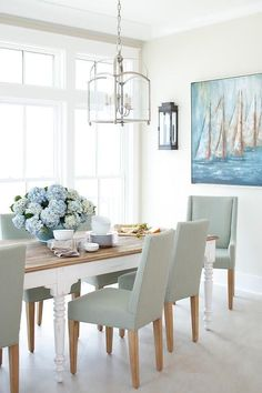 Large dining room windows invite lots of light shining on a white dining room table with a wood top embellished by blue floral arrangements.