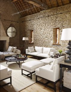 Loving this stacked stone wall with the juxtaposition of the linear white furniture... A clean, inviting space.