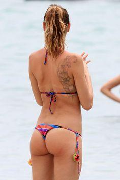 Anche la nazional-popolare Melissa Satta usa il bikini come indumento che calamita l'attenzione. Ma più che sul suo lato b già noto a molti, l'occhio cade sull'enorme tatuaggio con fiori e sciame di farfalle che ha sulla spalla.