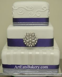 Three tier square white fondant custom modern wedding cake design idea with stripes, curlicues, purple and silver ribbons and pearl brooch