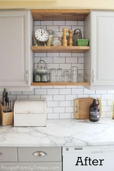 Painted grey kitchen cabinets in Sherwin Williams Pussywillow. White faux Carrara marble countertops. Wood open shelves. Handmade white subway tile backsplash. All DIY and on a tiny budget. #kitchenideas #makeover #farmhousekitchen