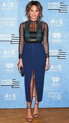 Chrissy Teigen in a sheer lace top and navy front-slit midi skirt