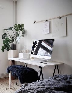 Bedroom, living room and workspace in one. White walls and simple clean interior design home office space.