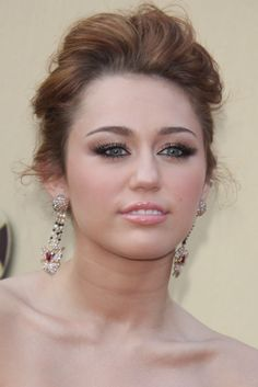 Miley Cyrus wearing a elegant updo hairstyle while attending the 2010 Oscars