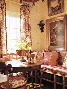 A lovely room in the French country style. Provincial furniture, epoch Charles X,  in walnut, settee with woven rush seat covered in toile de jouy fabric. Curtains and cushions in provincial prints, mainly checks and toile de jouy in dark red on cream. Painted tole cache pot (planter).