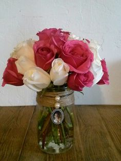 Wedding Table Bouquet idea. Mason Jars wrapped in jute with a small frame of lived ones who could not attend ceramony ot who have passed.