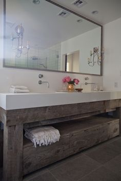 Beautiful bathroom features salvaged wood double vanity topped with thick white countertop paired with wall-mounted faucets and gray…
