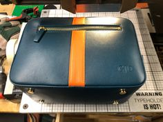 embossing initials onto a Stow leather washbag