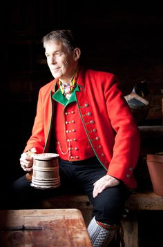 He reminds me of my grandfather... Hardanger Folkemuseum, Norway. The mens bunad jacket and waistcoat are made from red woolen cloth with green edging, decorated with plenty of forged silver buttons. Used on special occasions are the silver ring, watch chain, and the colorful silk scarf. The wooden goblet, like the one he is holding, was used all over all over Scandinavia.