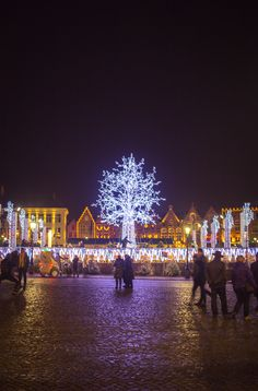Lit up ice rink and Christmas Market in the Markt in Brugge (Bruges), Belgium in winter for Christmas