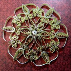 This snowflake ornament is 3 5/8 in diameter. Made by master quiller Heidi Bishop. It hangs by invisible thread. Made from antique cream color