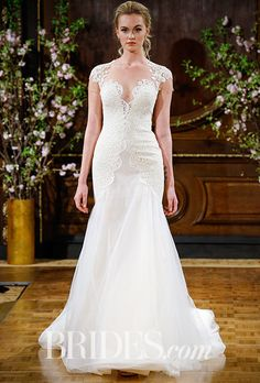 """Brides.com: . """"Toni"""" fit and flare gown with cap sleeve illusion yoke with floral appliqué. Tulle skirt with lace appliqués, Isabelle Armstrong"""