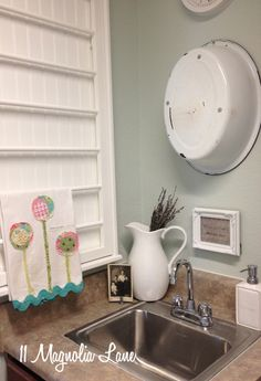 Small laundry room redo with Sherwin-WIlliams Sea Salt paint, vintage white and enamelware decor, and lots of tricks to maximize space and function.
