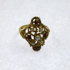 An antique vintage garnet and pearl filigree ring made in 9ct yellow gold. The ring features four facet cut garnets and five subtle pearls on a diamond shaped filigree head. It has some shoulder detail and is truly an attractive ring in such good condition.  Ref:- 122  Details:-  Size - 0 Weight - 3.85 grams Date Vintage  Genuine offers will be considered.  A nice presentation box will be supplied and gift wrap.  I always hand pick my antique and vintage jewellery to ensure they are in good…