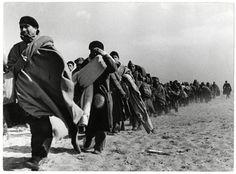 Refugiados .Refugiados cargados con sus enseres y caminando por la playa. (Robert Capa)