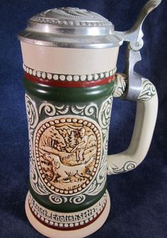 "1978 Strike at Point Sporting Avon Beer Stein - This is a beautiful collectible beer stein produced by Avon in 1978.  It features a hunting scene with an English Setter on one side and a trout on the other side.   This item is in excellent condition and is approximately 9"" tall and weighs a little over two pounds."