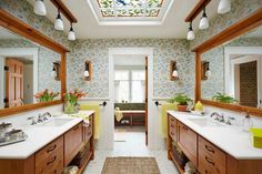 A raised roof with large shed dormers added height and width for a two-part bath suite. Custom woodwork, marble countertops, and unfussy floral wallpaper elevate the cabin aesthetic.