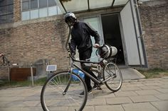 """Artist Matt Hope, wearing a helmet, pushes his air filtration bike out of his studio on a hazy day in Beijing, on March 26, 2013. Using an IKEA perforated garbage can, moped helmet, fighter-pilot breathing mask, wheel-powered generator and home air filtration system, Beijing-based artist Matt Hope built a """"breathing bicycle"""" as a way of protecting himself from air pollution. (Reuters/Petar Kujundzic)"""