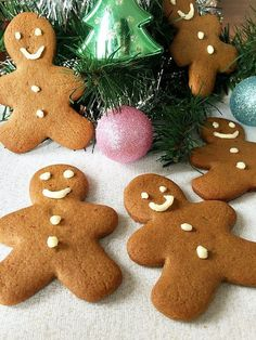 5 gingerbread men decorated with icing sugar around a christmas tree