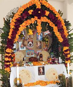 Marigolds and red cockscomb flowers (symbols of the blood of Christ) adorn a Day of the Dead altar. (mexican-folk-art-guide.com via @Nezka Pfeifer)