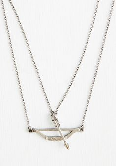 When dressing up an outfit, you aim for on-target accessories such as this clever bow-and-arrow necklace! One chain of this metallic silver adornment suspends a horizontal bow, while the other holds a vertical arrow at the ready - bull's eye!