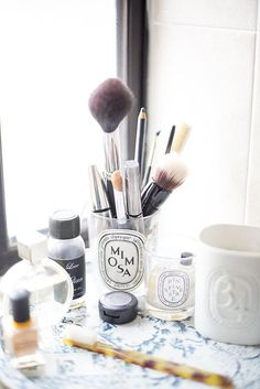 Repurpose pretty candle holders as a place to organize makeup brushes