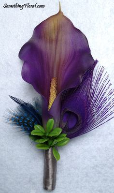 Realistic, artificial, purple calla lily boutonniere accented with a purple peacock feather, midnight blue pheasant feathers, green foliage, and a grey satin stem wrap. This was created for an Oregon couple's purple, midnight blue, and grey themed wedding.