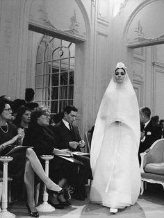 Dior, Robe Hyménée, collection Haute Couture printemps-été 1961, ligne Slim Look Le mannequin argentin Kouka Denis dans une robe de mariée dessinée par Marc Bohan (nommé directeur artistique pour remplacer Yves Saint Laurent à la fin de l'année 1960), dans le Grand Salon de la maison Dior.  Arrivée en France en 1956, elle se fait repérer par Yves Saint Laurent qui en fait sa muse et le mannequin vedette de la marque.