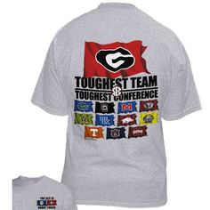 """UGA Toughest Team Conference Tee. University of Georgia oxford gray t-shirt with large Georgia G logo on red flag above text reading """"TOUGHEST TEAM TOUGHEST CONFERENCE"""" above SEC team flags. SEC & Georgia flag on front left of tee with text reading """"THE SEC IS DAWG TOUGH""""."""