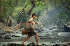 The Little fisherman - The Little fisherman boy walking in the creek for catch fish. Is Lifestyle of children in countryside Thailand.