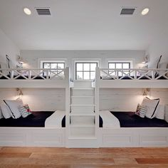 Cottage boys' bunk room features two sets of white built-in bunk beds dressed in navy bedding lined with distressed shiplap flanked by a built-in staircase.