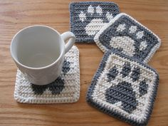 Paw Print Coasters. Gray and white crochet coaster set with dog paw prints. Pet lover mug rug by hooknsaw on Etsy https://www.etsy.com/listing/385841060/paw-print-coasters-gray-and-white