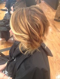 Light Blonde tone face framing and toned down darker blonde Balyage throughout rest of hair...angled bob styled using curling iron as a wand for a beachy look