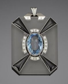 An art deco rock crystal, enamel, onyx and diamond pendant, circa 1920  The octagonal frosted rock crystal plaque, set to the centre with a large oval-cut aquamarine within a surround of single-cut diamonds and four pyramid-shaped onyx plaques, unsigned, French assay marks, pendant length 5.5cm.