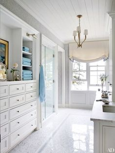 The master bath of a Maine home conceived by designer Suzanne Kasler and architect Les Cole boasts built-in cabinetry, custom-made mosaic tile by Waterworks, and light fixtures from Circa Lighting | archdigest.com