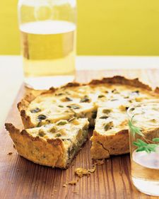 ZUCCHINNI QUICHE  All-purpose flour, for dusting  Tart Dough  2 tablespoons extra-virgin olive oil  1 tablespoon plus 1 teaspoon minced garlic  12 ounces zucchini (about 2 medium), trimmed and cut into 1/2-inch cubes  1 cup frozen shelled edamame, thawed  Coarse salt and freshly ground pepper  2 large eggs  1 cup heavy cream  1/2 cup milk  1 cup finely grated Pecorino Romano cheese (about 3 ounces)