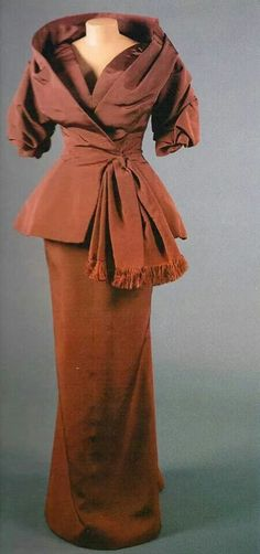 1954 evening ensemble, jacket has stand-away shawl collar over a narrow dress that tapers to a narrow hobble skirt