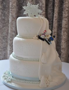 Winter Themed Wedding Cake with piped snowflakes and snowflakes topper. To the side is a snowy mountain scene complete with snowboarding lego figures!