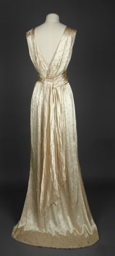 Dress [back view], England, 1934-35. Springhill Costume Collection © National Trust / Andrew Patterson. A presentation outfit consisting of a cream silk slipper satin long dress with a cowl neck line centre front, pleated into the centre back, with a decoration of random wavy tucks and scattered claw set, flat backed diamante all over. Cut to a slight train centre back, the dress is straight with a normal waist. An elegant dress. The detachable train gives it a second use as an evening…