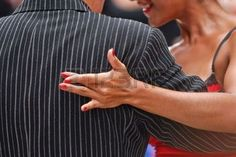 tango: Female hand on the back of a pin striped suit of a tango couple in Buenos Aires, Argentina.