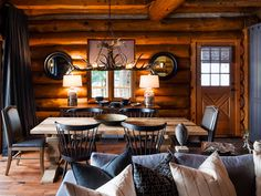 Modern black Windsor and gray leather chairs now gather around an outsized, rough hewn wooden table, while a faux antler chandelier floats proudly above, providing atmosphere and adjustable illumination at the twist of a button. RELATED: 64 Dining Room Decorating Ideas