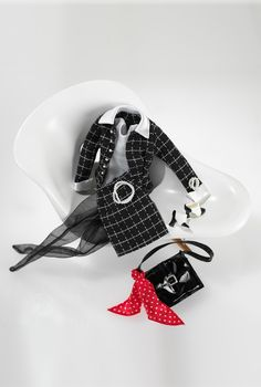 Executive Lunch™ Fashion | Barbie Collector The Executive Lunch™ Barbie® doll fashion was part of the 1999 membership kit for The Official Barbie Collector's ClubSM. The ensemble included a Chanel-esque woven black and white suit, a white body suit, sheer black stockings, black and white spectator heels, faux pearl jewelry, and a black purse accented with a red handkerchief with white polka dots.