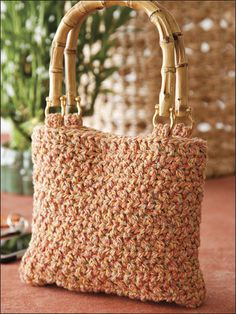 """Recycled cotton yarn and bamboo handles make this quick-to-stitch tote a stylish eco-conscious choice. This e-pattern was originally published in the June 2010 issue of Crochet World magazine. Size: 9"""" x 8"""", excluding handles. Made with medium (worsted) weight yarn and sizes H/8/5mm and J/10/6mm hooks. Skill Level: Easy"""