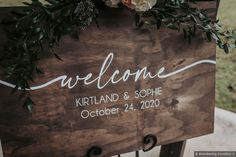 Dark wooden sign with white painted names and dates, green leaf decor Spencer Iowa, Memphis Botanic Garden, Fall Wedding, Rustic Wedding, Signature Cocktail, Wedding Signage, Wedding In The Woods, White Paints, Botanical Gardens