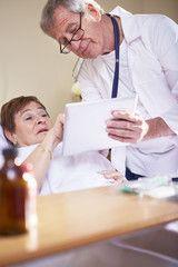 Doktor, mit Tablet-PC bei älterer Frau im Krankenhausbett