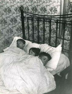 Children sleeping 3-to-a-bed in a damp room at Hanbury Buildings, Poplar, 1939. Hanbury was a slum tenement block where the landlord had fai...