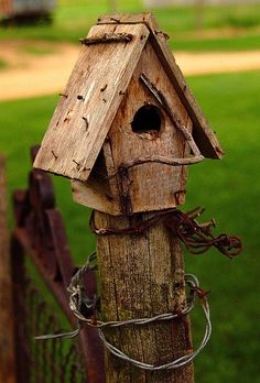 pretty birdhouse on  fence post..